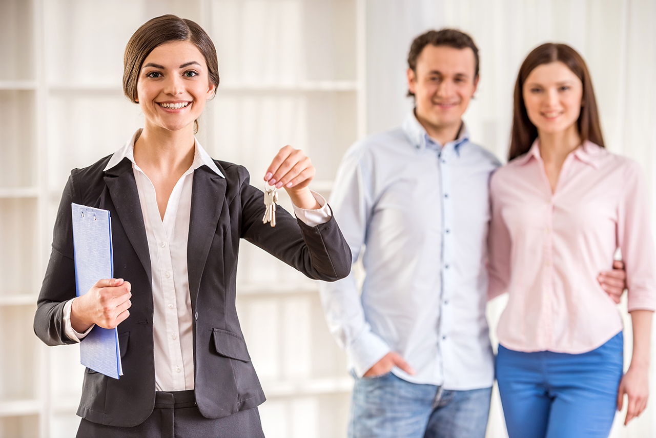 realtor holding keys with a couple in the background