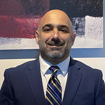 a picture of Jeff in a blue suit in front of a white, red, and blue wall