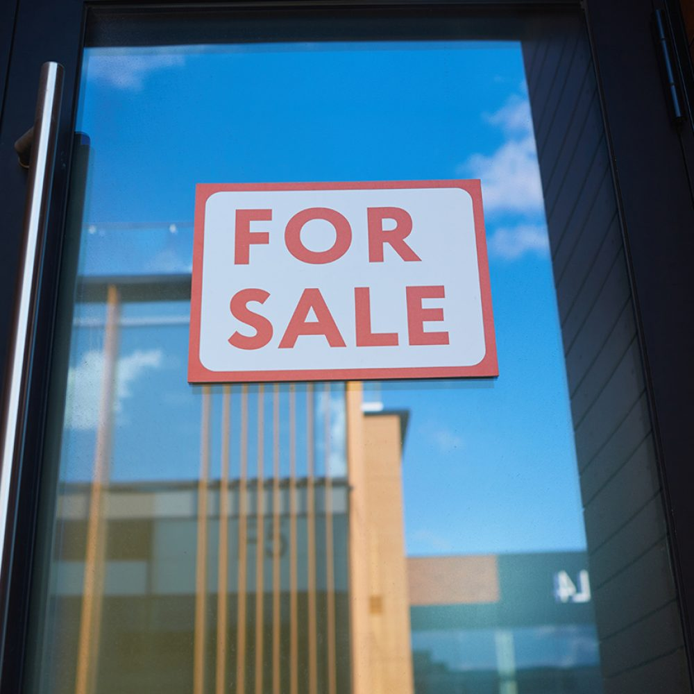 For Sale sign on a glass door