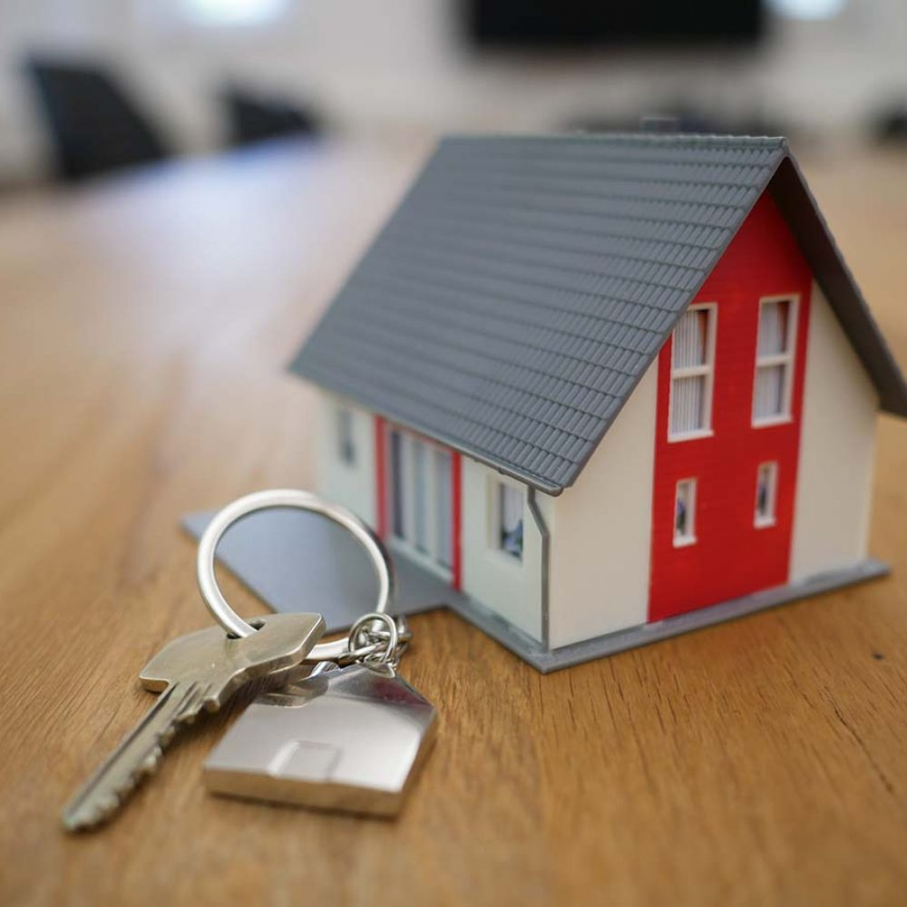 mini house on a table with a key next to it